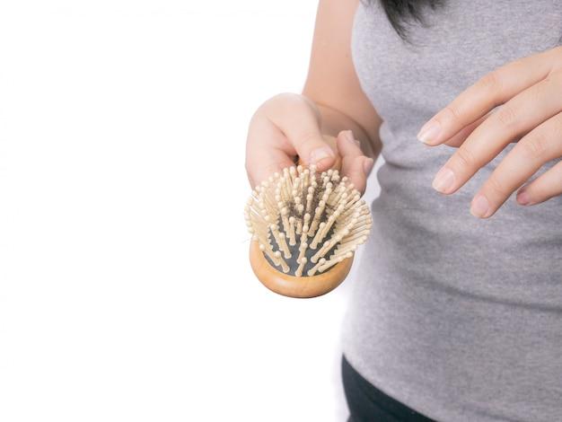 Volwassen aziatische vrouwen ernstig met haarprobleem die kam en haar gespleten punten bij de hand houden.