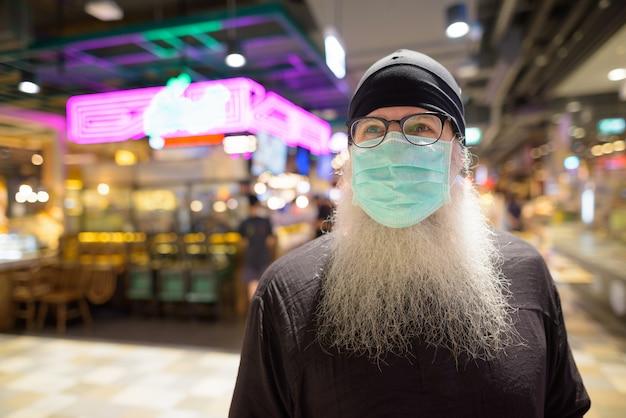 Volwassen bebaarde hipster man denken met masker voor bescherming tegen corona virusuitbraak in het winkelcentrum