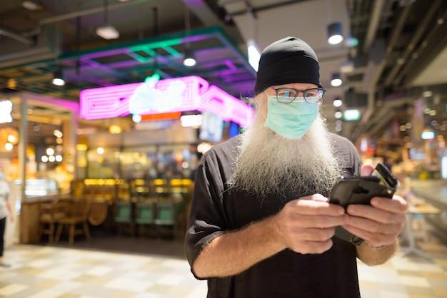 Volwassen bebaarde hipster man met telefoon met masker voor bescherming tegen corona virus uitbraak in het winkelcentrum
