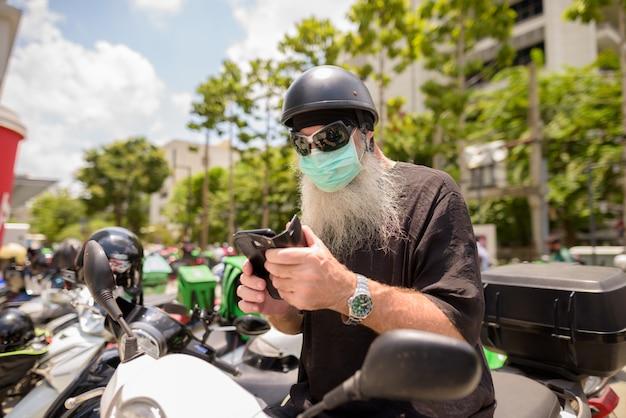 Volwassen bebaarde hipster man met zonnebril en masker met behulp van telefoon zittend op de motorfiets