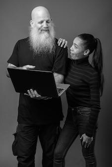 Volwassen bebaarde kale man en jonge mooie aziatische vrouw samen tegen grijze muur in zwart-wit