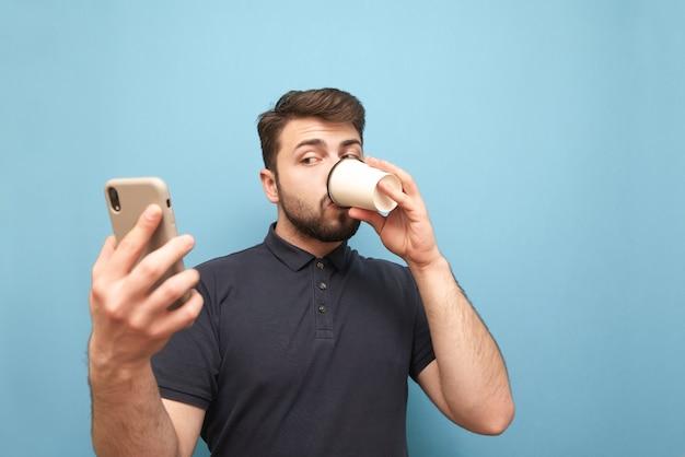 Volwassen bebaarde man drinkt koffie uit een papieren beker en gebruikt een smartphone op blauw
