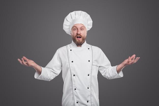 Volwassen bebaarde man in uniform van de chef gebaren en camera kijken met verbazing tegen de grijze achtergrond