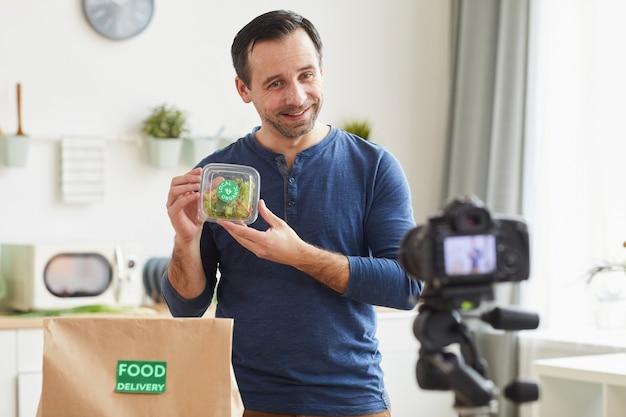 Volwassen bebaarde man met biologische salade box tijdens het opnemen van de beoordeling van de bezorgservice van het eten in het interieur van de keuken