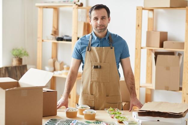 Volwassen bebaarde man schort dragen en glimlachend permanent door houten tafel met individuele etensporties klaar voor verpakking, werknemer in de bezorgdienst van eten