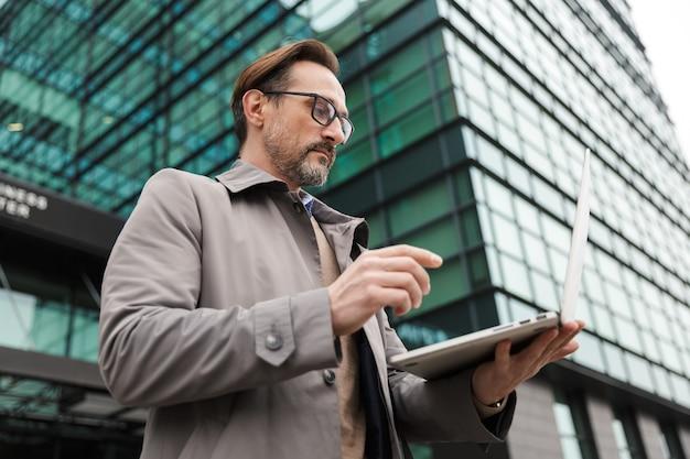 Volwassen bebaarde zakenman in bril met laptop terwijl hij in de buurt van kantoorgebouw in stedelijk gebied staat