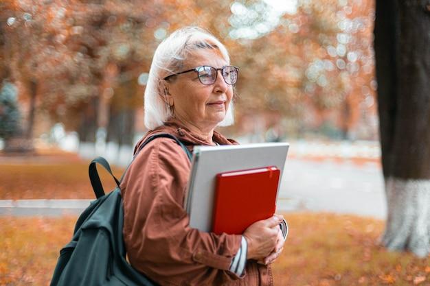 Volwassen blanke blonde leraar vrouw in casual kleding staat met notebooks en rugzak wandelen in het herfst park