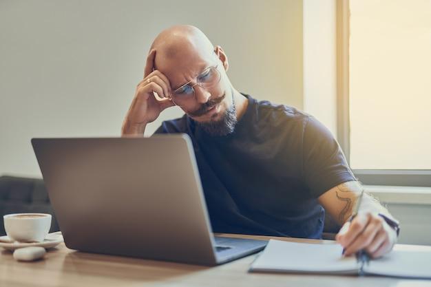 Volwassen blanke kale man-manager die laptop gebruikt tijdens het schrijven van notities in notitieblok op de werkplek