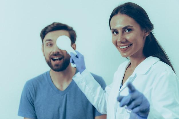 Volwassen blanke man bij de receptie op vrouwelijke arts