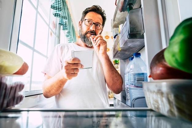 Volwassen blanke man die een notitielijst neemt van voedsel dat thuis in de open koelkast kijkt - keukenactiviteit en alternatief oogpunt - marktwinkelen en quarantainevergrendeling thuisblijven coronavirustijd