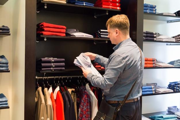 Volwassen blanke man kijkt tussen de rijen kleren aan een hanger zijn geschikte maat kleren.