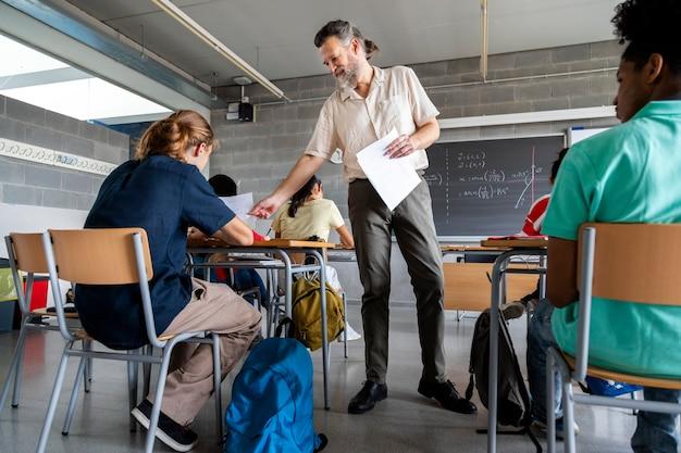 Volwassen blanke man leraar deelt vellen papier uit aan multiraciale middelbare scholieren. onderwijsconcept.
