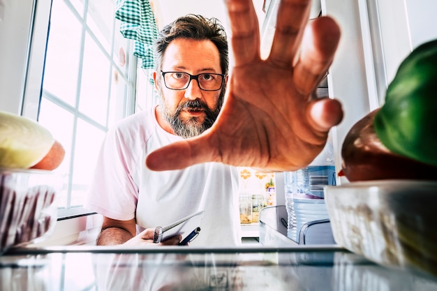 Volwassen blanke man neemt gezond voedsel uit een open koelkast - close-up binnenaanzicht - gewichtsverliesconcept - thuisactiviteit in de keuken - quarantaine coronavirus mensenconcept blijf thuis