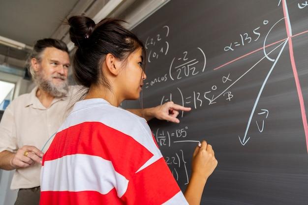 Volwassen blanke mannelijke wiskundeleraar op de middelbare school legt schoolbordoefening uit aan student