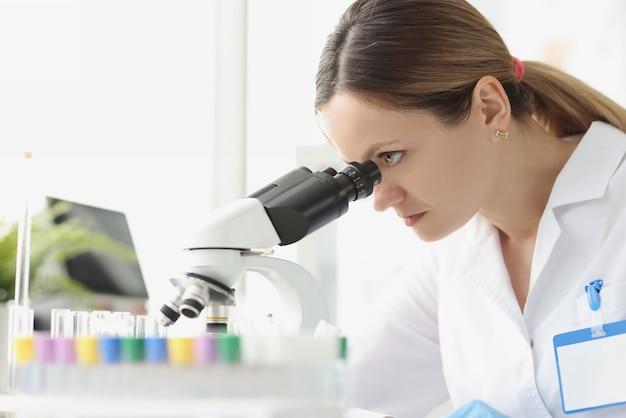 Volwassen blanke schoonheid vrouw scheikundige kijken naar microscoop beroep wetenschapper concept