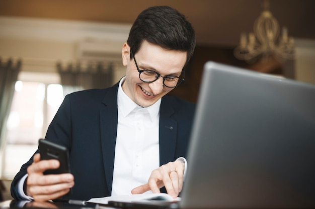 Volwassen blanke werknemer doet papierwerk glimlachend terwijl hij een smartphone in zijn hand houdt.