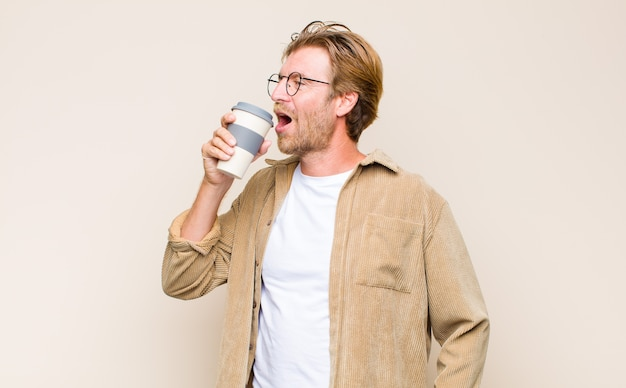 Volwassen blonde man met een hete koffie