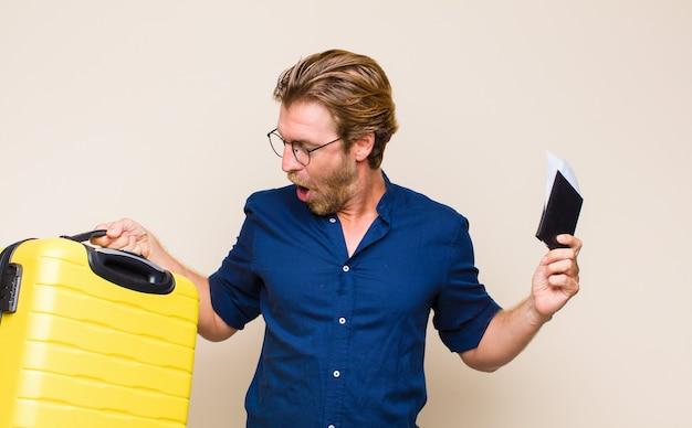 Volwassen blonde man met een koffer. reis concept.