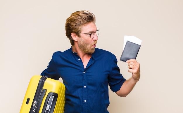 Volwassen blonde man met een koffer
