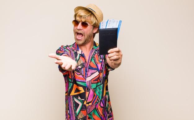Volwassen blonde man met een paspoort en vliegtickets