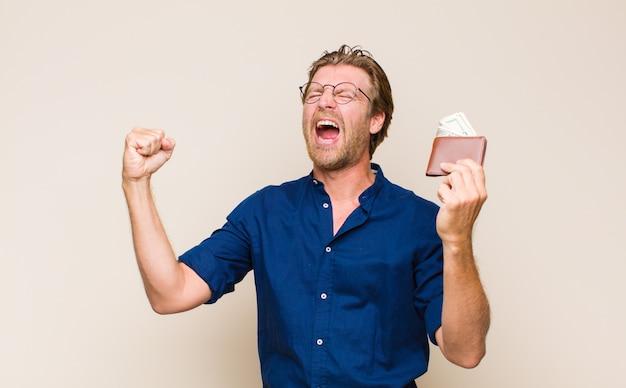 Volwassen blonde man met een portemonnee en dollarbankbiljetten