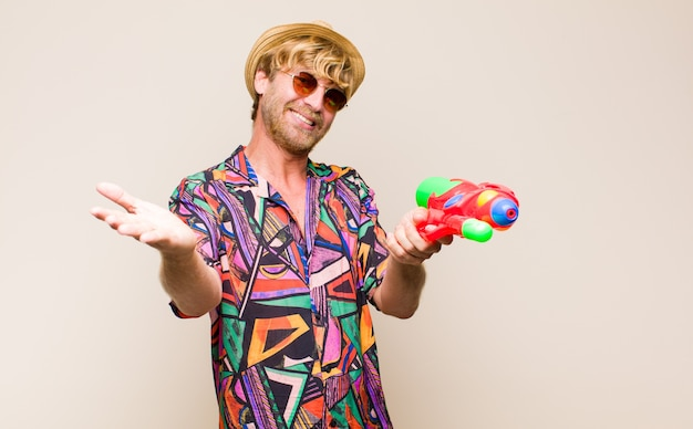 Volwassen blonde man op vakantie met een waterpistool