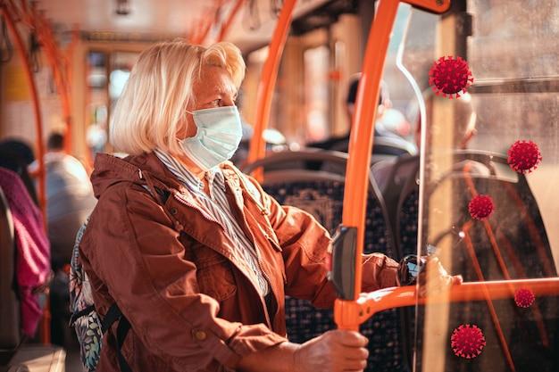 Volwassen blonde oude vrouw die een medisch beschermend masker draagt in het openbaar vervoer