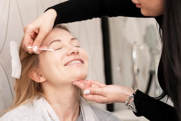 Volwassen blonde vrouw die make-up in een schoonheidssalon doet. detailopname.