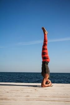 Volwassen blonde vrouw met kort kapsel praktijken yoga op de pier