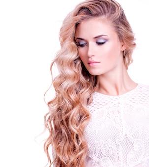 Volwassen blondemeisje met lang blond krullend haar. portret van een mooie vrouw over witte muur.
