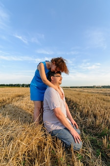 Volwassen boer en vrouw brengen tijd door in het veld. de man zit. een vrouw staat naast hem en omhelst hem. een vrouw kust haar man op het hoofd.