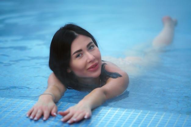 Volwassen brunette ontspanning ligt in geothermisch water in het zwembad in het kuuroord
