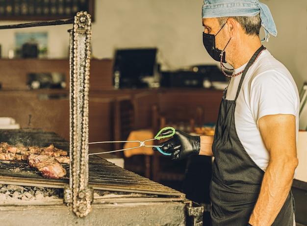 Volwassen chef-kok die gezichtsmasker en haarnet draagt dat vlees in de grill kookt en vleestang gebruikt.