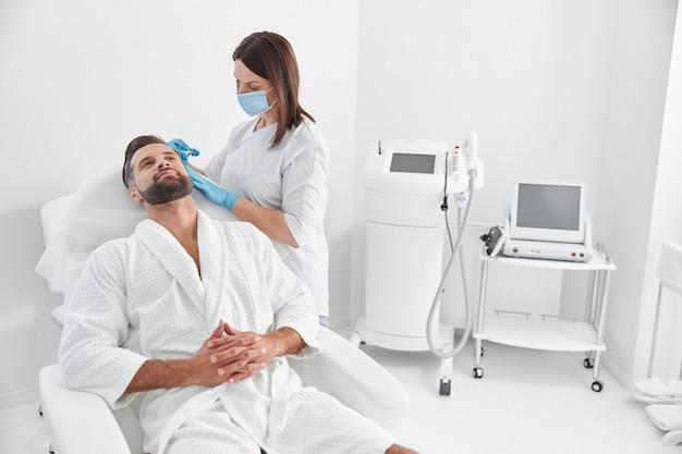 Volwassen cliënt zit in een fauteuil terwijl schoonheidsspecialist mesotherapie uitvoert in schoonheidssalon
