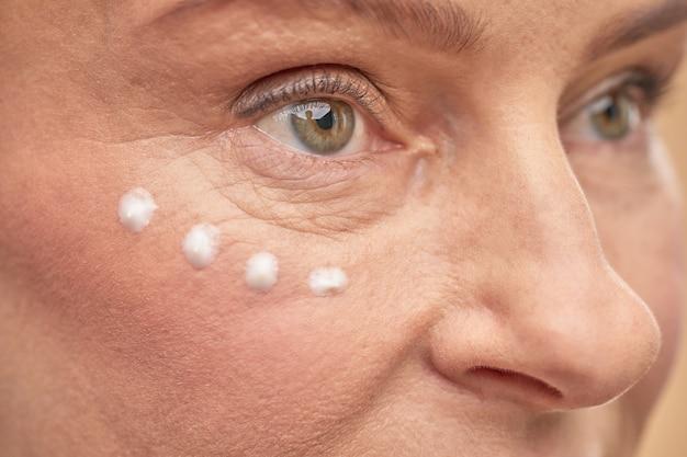Volwassen dame die anti-verouderingscrème aanbrengt om de huid te hydrateren