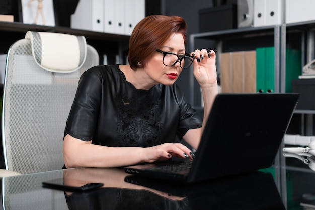 Volwassen de handglazen van de vrouwenholding en het kijken door hen in monitor in bureau