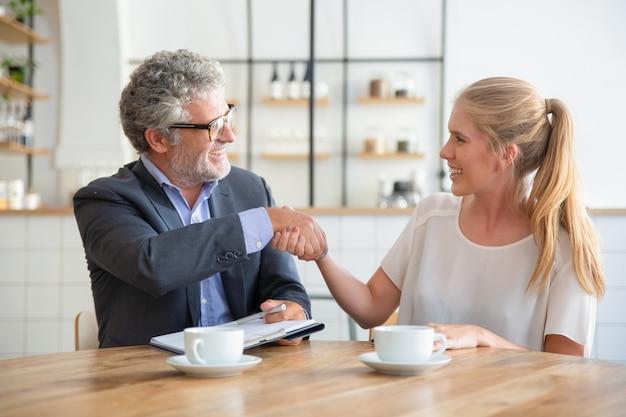 Volwassen deskundige ontmoeting met jonge klant tijdens een kopje koffie bij co-working, documenten vasthouden en handen schudden