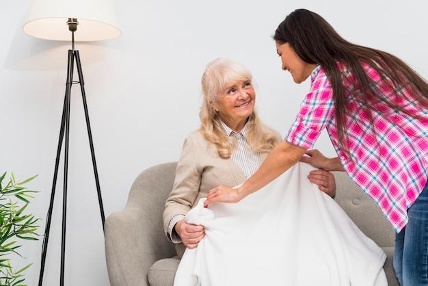 Volwassen dochter die deken over de glimlachende hogere moederzitting op bank thuis zetten