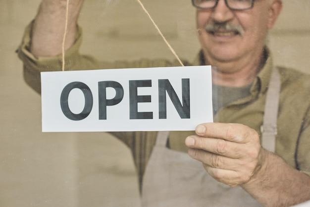 Volwassen eigenaar van winkel of café die open bord op de deur zet