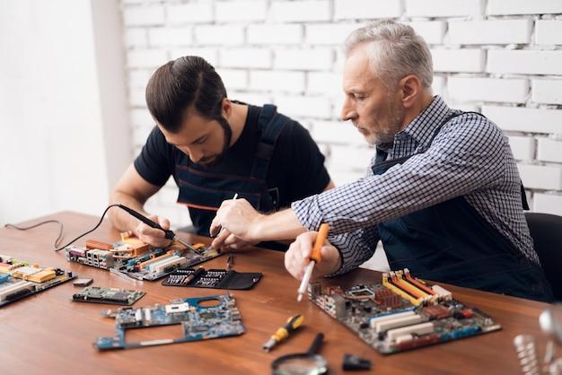 Volwassen en jonge mannen repareren delen van de computer samen