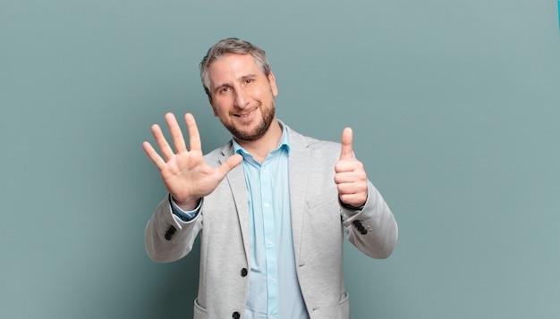 Volwassen en zakenman die vriendelijk glimlacht kijkt, nummer zes of zesde met vooruit hand toont, aftellend