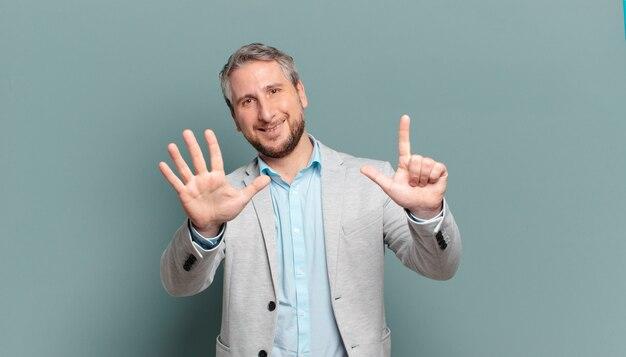 Volwassen en zakenman die vriendelijk glimlacht kijkt, nummer zeven of zevende met vooruit hand toont, aftellend