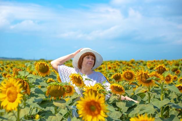 Volwassen europese vrouw in een witte hoed op een veld met zonnebloemen