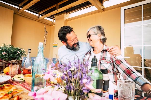 Volwassen familie mensen genieten van de vrijetijdsbesteding samen eten en plezier hebben - mensen met eten en drinken thuis - vrolijke senior moeder en volwassen zoon glimlachen en houden van elkaar - gelukkige levensstijl