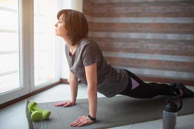 Volwassen fit slanke vrouw heeft thuis training. ernstige volwassen vrouwelijke persoon staat op yoga-positie om kracht en welzijn te krijgen. alleen sporten.