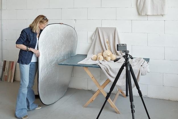 Volwassen fotograaf in denim outfit verlichting reflector aanpassen tijdens het voorbereiden van fotoshoot van voedselsamenstelling