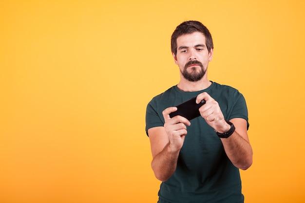 Volwassen gamer die videogames speelt op zijn smartphone op gele achtergrond in de studio. vrijetijdsbesteding