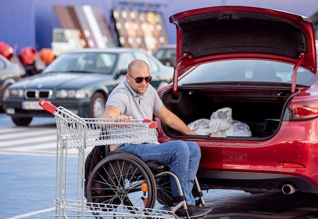 Volwassen gehandicapte man in een rolstoel doet aankopen in de kofferbak van een auto op de parkeerplaats van een supermarkt