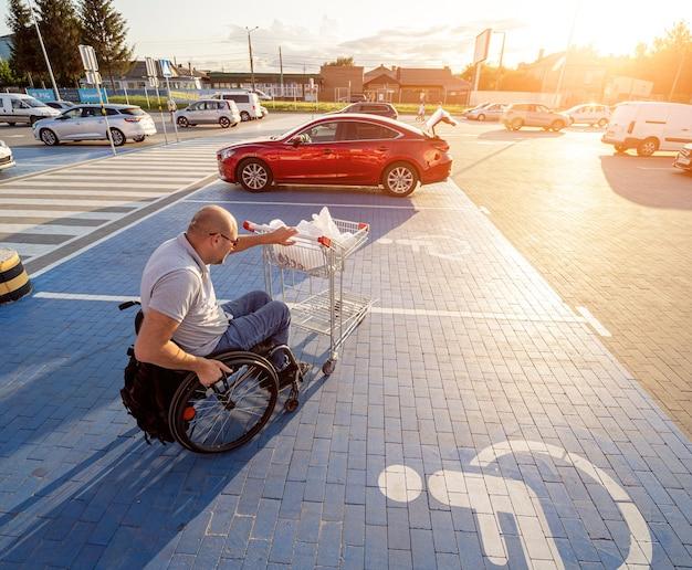 Volwassen gehandicapte man in een rolstoel duwt een kar naar een auto op de parkeerplaats van een supermarkt