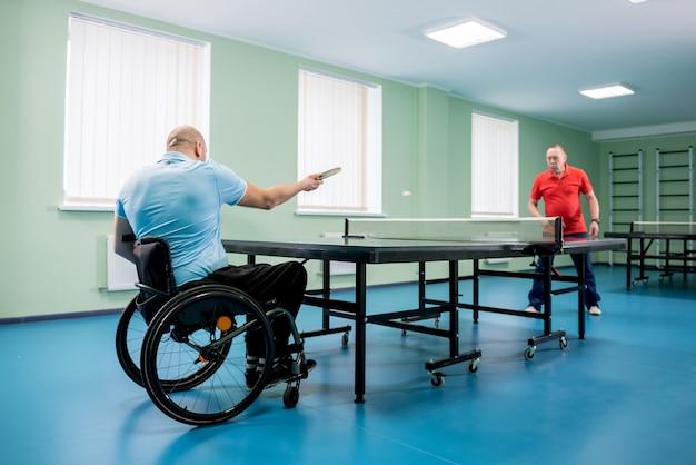 Volwassen gehandicapte man in een rolstoel speelt tafeltennis met zijn coach